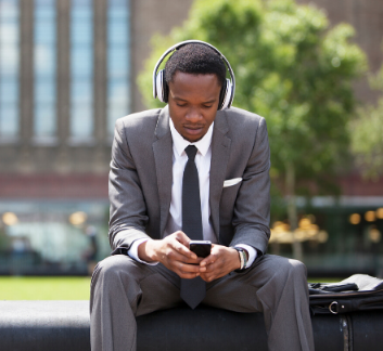 young professional sitting outside listening to device with headphones