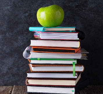 Image of a green apple on top of a stack of books