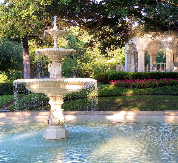 Photo of a fountain in a park with gazebo in the background